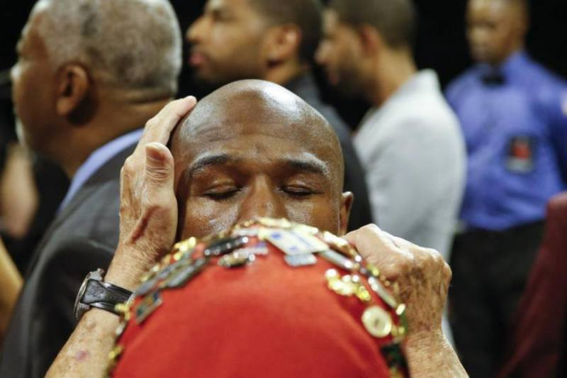 Floyd Mayweather Jr. is attended to before his welterweight title fight against Andre Berto Saturday, Sept. 12, 2015, in Las Vegas. (AP Photo/John Locher)