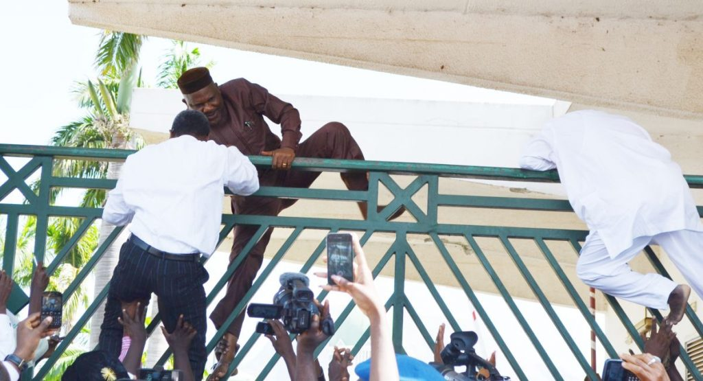 MEMBERS OF THE HOUSE OF REPRESENTATIVES CLIMBING THE  NATIONAL ASSEMBLY GATE DURING A FRACAS AT THE NATIONAL ASSEMBLY IN  ABUJA ON THURSDAY (20/11/14). 5824/20/11/2014/CH/AIN/NAN - NASS
