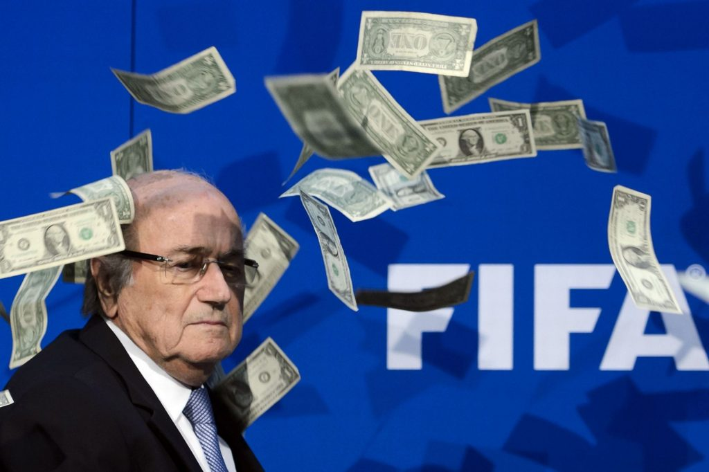 Lee-Nelson-throws-fake-money-at-Sepp-Blatter-during-FIFA-press-conference