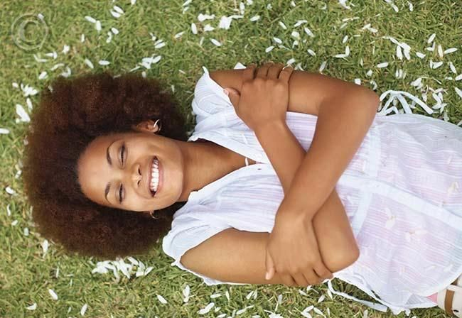 young_black_woman_relaxing_on_grass_happy_free